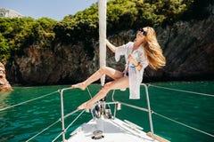 Sexig lång hårkvinna i swimwear som seglar pittoreskt landskap Royaltyfri Bild