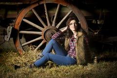 Sexig lantgårdflicka som framme poserar av den lantliga vagnen i ladugård Arkivfoto