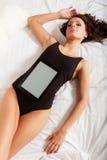Sexig lat flicka som ligger med minnestavlatouchpaden på säng Arkivbild
