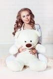 Sexig mörk blond flicka som kramar nallebjörnen Fotografering för Bildbyråer