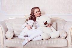 Sexig mörk blond flicka som kramar nallebjörnen Royaltyfri Fotografi