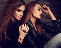 Sexig makeup två härliga modeller som sitter i profil på gata w arkivfoton