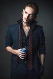 Sexig man med en cigarett och en drink i ett tenn Fotografering för Bildbyråer