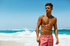Sexig man på stranden i sommar Manligt avslappnande near hav arkivbild