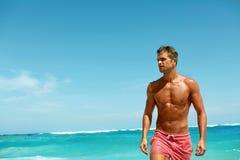 Sexig man på stranden i sommar Manligt avslappnande near hav arkivbilder