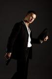 Sexig man som poserar som mafiosi, på grå bakgrund Royaltyfri Fotografi