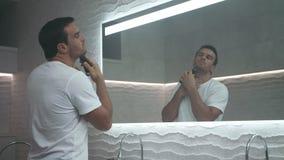 Sexig man som rakar skägget i bad Ansa av den allvarliga mannen som rakar i badrum arkivfilmer