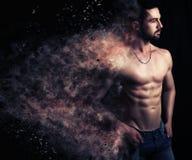 Sexig man som skapar en explosion av partiklar Royaltyfri Fotografi
