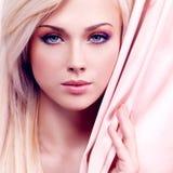 Sexig mjuk kvinna med rosa silke. Arkivfoto