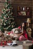 Sexig modell som kläs som jultomten med en svart krona nära en julgran som rymmer en björn Arkivbild
