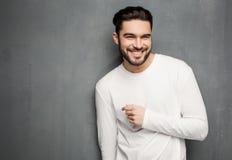 Sexig modemanmodell i den vit tröjan, jeans och kängor som ler mot väggen royaltyfria foton