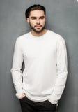 Sexig modemanmodell i vitt posera för tröja som, för jeans och för kängor är dramatiskt arkivbilder