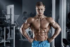 Sexig muskulös man i idrottshall som utarbetar, format buk- Stark manlig naken torsoabs fotografering för bildbyråer