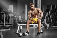 Sexig muskulös man i idrottshallen, format buk- Stark manlig naken torsoabs som utarbetar arkivbild