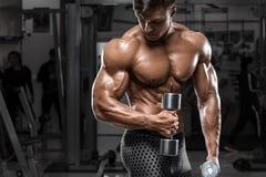 Sexig muskulös man i idrottshallen som gör övningen för biceps Stark manlig naken torsoabs som utarbetar fotografering för bildbyråer