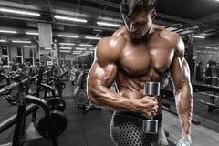 Sexig muskulös man i idrottshallen som gör övningen för bicepsl Stark manlig naken torsoabs som utarbetar fotografering för bildbyråer