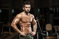 Sexig muskulös man som poserar i idrottshallen, format buk- Stark manlig naken torsoabs som utarbetar royaltyfri bild
