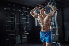 Sexig muskulös man som poserar i idrottshallen, format buk- Stark manlig naken torsoabs som utarbetar Arkivbild
