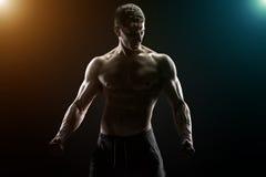 Sexig muskulös man som poserar med den nakna torson på svart bakgrund Arkivfoto