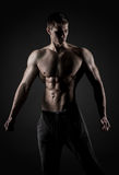 Sexig muskulös man som poserar med den nakna torson på svart bakgrund Fotografering för Bildbyråer