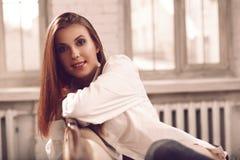 Sexig och attraktiv ung kvinna med långt hårsammanträde på soffan i behå arkivbild