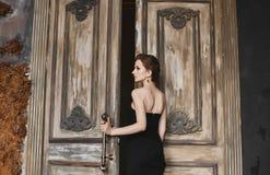 Sexig och härlig brunettmodellflicka med en moderiktig frisyr och med ljus makeup, i en trendig svart åtsittande klänning royaltyfri bild