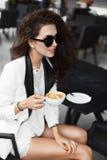 Sexig och trendig brunettmodellflicka med yrkesmässig makeup och stilfull solglasögon, i vita kortslutningar, i blus och i en stå royaltyfri fotografi