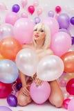 Sexig platinablond kvinna som poserar med ballonger Arkivbild