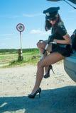Sexig poliskvinna på vägen Arkivfoto