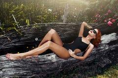 Sexig rödhårig mankvinna med svart solglasögon Arkivbild