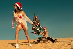 Sexig Santa hjälpreda som drar Santa på stranden Arkivfoto
