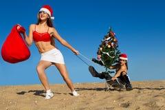 Sexig Santa hjälpreda som drar Santa på stranden Royaltyfri Bild
