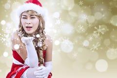 Sexig Santa slående snow på defocused lampor Royaltyfri Foto