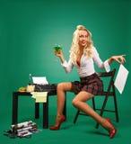 Sexig sekreterare för utvikningsflicka på mottagandet nära skrivmaskinen arkivbild