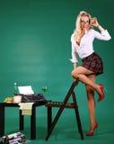 Sexig sekreterare för utvikningsflicka på mottagandet nära skrivmaskinen royaltyfri bild