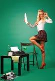 Sexig sekreterare för utvikningsflicka på mottagandet nära skrivmaskinen royaltyfri fotografi