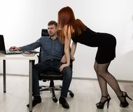 Sexig sekreterare som flörtar med framstickandet i arbetsplatsen sextrakasseri och kontorsmissbrukbegrepp royaltyfri bild