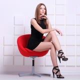 sexig sittande kvinna för stol skjutit mode arkivbild