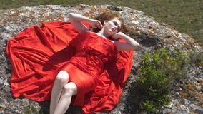 Sexig skönhet med snövit hud i rött frodigt i solljuset stock video