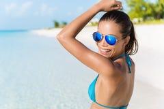 Sexig solglasögonbikinikvinna som har gyckel på stranden Royaltyfri Fotografi