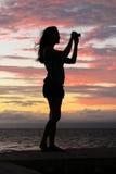 Sexig solnedgångkontur av kvinnan som tar foto Royaltyfria Bilder