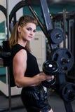 Sexig sportig kvinna som gör maktkonditionövning på sportidrottshallen Härlig flicka som utarbetar i idrottshall Arkivfoto