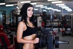 Sexig sportig kvinna som gör maktkonditionövning på sportidrottshallen Härlig flicka som utarbetar i idrottshall Fotografering för Bildbyråer