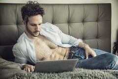 Sexig stilig ung man i säng med bärbar datordatoren Arkivbilder