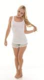 Sexig ung blond kvinna i vita ärmlös tröja och kortslutningar Royaltyfri Bild