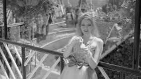 Sexig ung blond kvinna som blåser såpbubblor i blommaträdgård Den nätta drömma gulliga flickan i roligt snör åt klänningen koppla lager videofilmer
