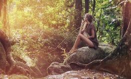 Sexig ung dam som vilar i den tropiska skogen arkivbilder