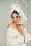 Sexig ung flicka med mörkt hår, stora ögon och mörka ögonbryn som bär den vita handduken för whith för badämbetsdräkt på hennes h Arkivbilder