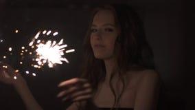 Sexig ung flicka som har gyckel och dansar med tomtebloss på partiet arkivfilmer