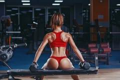sexig ung friidrottflicka med perfekta bakdelar som vilar efter övningar i idrottshall Royaltyfri Bild
